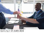 Купить «Business people holding an American flag at conference registration table», фото № 31649404, снято 16 марта 2019 г. (c) Wavebreak Media / Фотобанк Лори