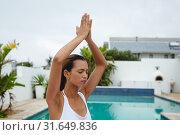 Купить «Woman performing yoga near swimming pool in the backyard», фото № 31649836, снято 19 марта 2019 г. (c) Wavebreak Media / Фотобанк Лори