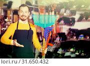 Купить «Seller displaying various items in garden equipment shop», фото № 31650432, снято 2 марта 2017 г. (c) Яков Филимонов / Фотобанк Лори