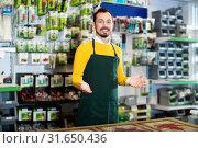 Купить «Seller displaying various items in garden equipment shop», фото № 31650436, снято 2 марта 2017 г. (c) Яков Филимонов / Фотобанк Лори