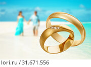 Two gold wedding rings with copy space. Concept on the theme of travel during the honeymoon. Photograph of jewelry made by stacking. Стоковое фото, фотограф Сергей Чайко / Фотобанк Лори