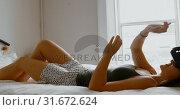 Woman using virtual reality headset on bed in bedroom 4k. Стоковое видео, агентство Wavebreak Media / Фотобанк Лори