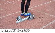 Купить «Female athlete taking starting position on running track 4k», видеоролик № 31672636, снято 17 апреля 2018 г. (c) Wavebreak Media / Фотобанк Лори
