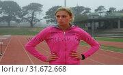 Купить «Front view of Caucasian female athlete walking on running track at sports venue 4k», видеоролик № 31672668, снято 17 апреля 2018 г. (c) Wavebreak Media / Фотобанк Лори