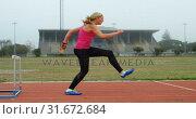 Купить «Side view of Caucasian female athlete jumping over hurdles on a running track 4k», видеоролик № 31672684, снято 17 апреля 2018 г. (c) Wavebreak Media / Фотобанк Лори