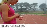 Купить «Side view of Caucasian female athlete using smartwatch on running track at sports venue 4k», видеоролик № 31672700, снято 17 апреля 2018 г. (c) Wavebreak Media / Фотобанк Лори