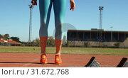 Купить «Front view of young female athlete exercising on a running track at sports venue 4k», видеоролик № 31672768, снято 17 апреля 2018 г. (c) Wavebreak Media / Фотобанк Лори