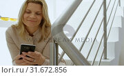 Купить «Woman using mobile phone on stairs at home 4k», видеоролик № 31672856, снято 24 августа 2018 г. (c) Wavebreak Media / Фотобанк Лори