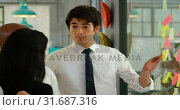 Купить «Business executives discussing over sticky note on glass wall 4k», видеоролик № 31687316, снято 1 сентября 2018 г. (c) Wavebreak Media / Фотобанк Лори