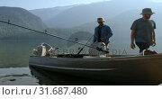 Купить «Two fishermen preparing for fishing in the river 4k», видеоролик № 31687480, снято 30 июля 2018 г. (c) Wavebreak Media / Фотобанк Лори