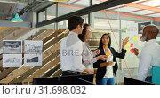 Купить «Executives discussing over sticky note on glass wall 4k», видеоролик № 31698032, снято 1 сентября 2018 г. (c) Wavebreak Media / Фотобанк Лори
