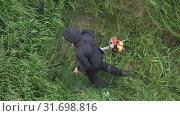 Купить «Мужчина косит зеленую траву ручной бензиновой газонокосилкой. Вид сверху, zoom in», видеоролик № 31698816, снято 17 июля 2019 г. (c) А. А. Пирагис / Фотобанк Лори
