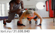 Купить «Trainer training female boxer in fitness studio 4k», видеоролик № 31698840, снято 6 сентября 2018 г. (c) Wavebreak Media / Фотобанк Лори