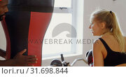 Купить «Female boxer practicing boxing in fitness studio 4k», видеоролик № 31698844, снято 6 сентября 2018 г. (c) Wavebreak Media / Фотобанк Лори