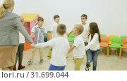 Купить «Group of happy children dancing in circle holding hands with their teacher in classroom during recess», видеоролик № 31699044, снято 18 декабря 2018 г. (c) Яков Филимонов / Фотобанк Лори