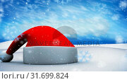Купить «Christmas hat in winter scenery and falling snow», видеоролик № 31699824, снято 2 ноября 2018 г. (c) Wavebreak Media / Фотобанк Лори