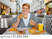 Купить «Fat woman eating high calorie food in restaurant», фото № 31699944, снято 24 мая 2019 г. (c) Tryapitsyn Sergiy / Фотобанк Лори