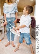 Купить «Little boy wrapped a housewife with wires», фото № 31700016, снято 28 мая 2019 г. (c) Tryapitsyn Sergiy / Фотобанк Лори