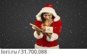 Купить «Video composition with falling snow over girl in santas suit holding gift», видеоролик № 31700088, снято 2 ноября 2018 г. (c) Wavebreak Media / Фотобанк Лори