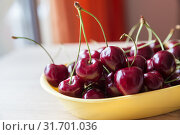 Купить «Ripe juicy red berries of a sweet cherry in a yellow bowl on the table by the window», фото № 31701036, снято 25 июня 2019 г. (c) Юлия Бабкина / Фотобанк Лори