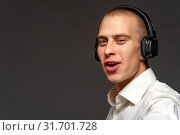 Купить «Smiling cheerful young guy with headphones», фото № 31701728, снято 16 июля 2020 г. (c) Pavel Biryukov / Фотобанк Лори