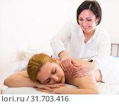 Купить «Aged massagist is doing relaxing massage shoulder area for young woman», фото № 31703416, снято 7 марта 2017 г. (c) Яков Филимонов / Фотобанк Лори