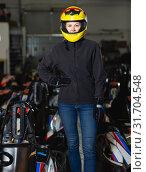 Купить «Young woman in helmet standing near sport cars», фото № 31704548, снято 18 марта 2019 г. (c) Яков Филимонов / Фотобанк Лори