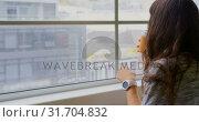 Купить «Businesswoman drinking coffee while sitting near window in office 4k», видеоролик № 31704832, снято 6 декабря 2018 г. (c) Wavebreak Media / Фотобанк Лори