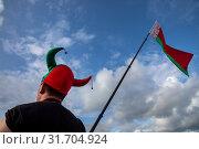 Купить «Болельщик в шапке цветов белорусского флага и с национальным флагом Республики Беларусь идет по улице», фото № 31704924, снято 20 июля 2019 г. (c) Николай Винокуров / Фотобанк Лори