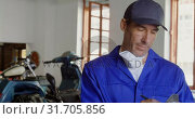 Купить «Male mechanic writing on clipboard in motorbike repair garage 4k», видеоролик № 31705856, снято 10 февраля 2019 г. (c) Wavebreak Media / Фотобанк Лори