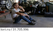 Купить «Male mechanic drinking coffee in motorbike repair garage 4k», видеоролик № 31705996, снято 10 февраля 2019 г. (c) Wavebreak Media / Фотобанк Лори