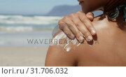Купить «Woman applying sunscreen on shoulders at beach in the sunshine 4k», видеоролик № 31706032, снято 14 февраля 2019 г. (c) Wavebreak Media / Фотобанк Лори