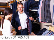 Купить «Smiling couple examining various suits in mens cloths store», фото № 31765108, снято 26 февраля 2020 г. (c) Яков Филимонов / Фотобанк Лори