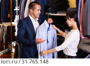 Купить «Seller helps buyer to choose a shirt in the store», фото № 31765148, снято 28 января 2020 г. (c) Яков Филимонов / Фотобанк Лори