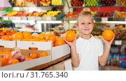 Купить «kid holding oranges at fruit section of store», фото № 31765340, снято 20 апреля 2019 г. (c) Яков Филимонов / Фотобанк Лори