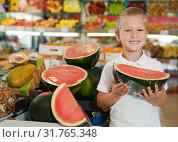 Купить «cute cheerful kid holding piece of watermelon at fruit section», фото № 31765348, снято 20 апреля 2019 г. (c) Яков Филимонов / Фотобанк Лори