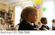 Купить «First-grader in glasses is on the lesson at his desk in the school», видеоролик № 31766568, снято 1 сентября 2018 г. (c) Aleksandr Sulimov / Фотобанк Лори