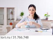 Купить «Young woman in budget planning concept», фото № 31766748, снято 8 января 2019 г. (c) Elnur / Фотобанк Лори