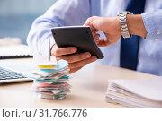 Купить «Young male employee in budget planning concept», фото № 31766776, снято 17 декабря 2018 г. (c) Elnur / Фотобанк Лори