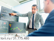 Купить «Businessmen trading stocks online. Stock brokers looking at graphs, indexes and numbers on multiple computer screens. Colleagues in discussion in traders office. Business success concept.», фото № 31775480, снято 9 июля 2020 г. (c) easy Fotostock / Фотобанк Лори