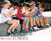 Купить «Eight kidsare chatting on their smartphone on walking», фото № 31798812, снято 8 апреля 2020 г. (c) Яков Филимонов / Фотобанк Лори