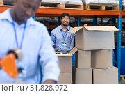 Купить «Male staff looking at camera while checking stock in warehouse», фото № 31828972, снято 23 марта 2019 г. (c) Wavebreak Media / Фотобанк Лори