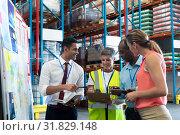 Купить «Warehouse staffs discussing over clipboard in warehouse», фото № 31829148, снято 23 марта 2019 г. (c) Wavebreak Media / Фотобанк Лори