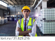 Купить «Male staff in hardhat and reflective jacket standing with arms crossed in warehouse», фото № 31829216, снято 23 марта 2019 г. (c) Wavebreak Media / Фотобанк Лори