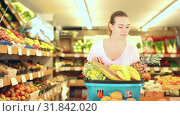 Купить «Cheerful woman standing with full shopping cart during shopping in fruit store», видеоролик № 31842020, снято 26 мая 2019 г. (c) Яков Филимонов / Фотобанк Лори