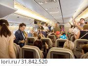 Пассажиры чартерного рейса готовятся к выходу из самолета (2019 год). Редакционное фото, фотограф Юлия Бабкина / Фотобанк Лори