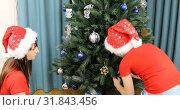 Купить «Boy with mom in christmas caps decorate new year tree», видеоролик № 31843456, снято 25 ноября 2018 г. (c) Aleksandr Sulimov / Фотобанк Лори