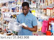 Купить «seller organizing assortment of items on shelves and racks», фото № 31843908, снято 21 января 2019 г. (c) Яков Филимонов / Фотобанк Лори