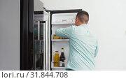 Купить «man taking apple from fridge at home kitchen», видеоролик № 31844708, снято 21 июля 2019 г. (c) Syda Productions / Фотобанк Лори