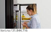 Купить «woman making list of necessary food at home fridge», видеоролик № 31844716, снято 21 июля 2019 г. (c) Syda Productions / Фотобанк Лори